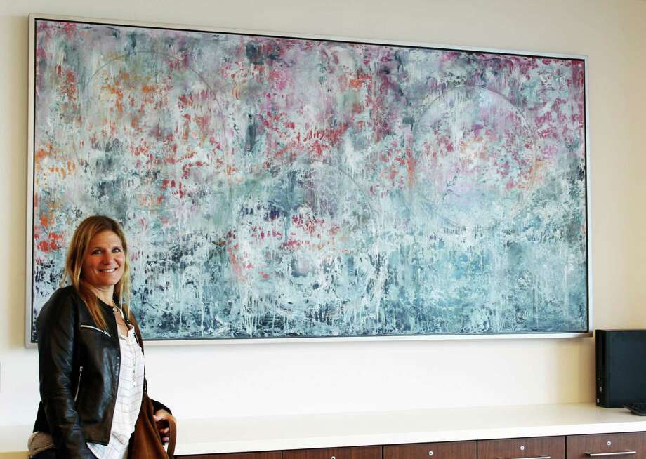 Andrea Bonfils of Darien, Conn. poses with her painting in a conference room in the new Stamford Hospital on Sept. 27, 2016. Photo: Erin Kayata / Hearst Connecticut Media / Darien News
