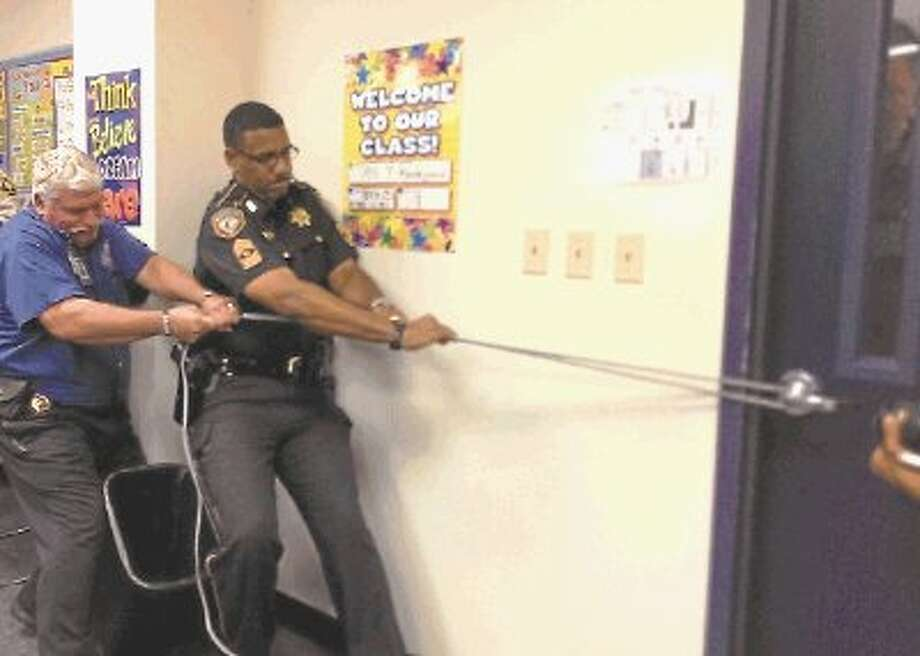 """(left) Sgt. Jeffery McGowen, Harris County Sheriff's Office and Thomas C. Petty, senior inspector/department outreach coordinator for the Harris County Fire Marshal's Office, use an extension cord to prevent an intruder from entering the classroom during """"Intruderology"""" training at Harris County Department of Education. / @WireImgId=2638613"""
