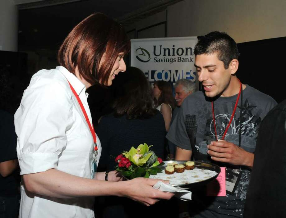 Stacey Hathaway of Shelton offers an hors d'oeure to Filmaker Justin Morales of Manchester during a Connecticut Film Festival party Tuesday at the Palace Theater in Danbury. The party was a benefit for Ability Beyond Disability. Photo: Lisa Weir / The News-Times Freelance