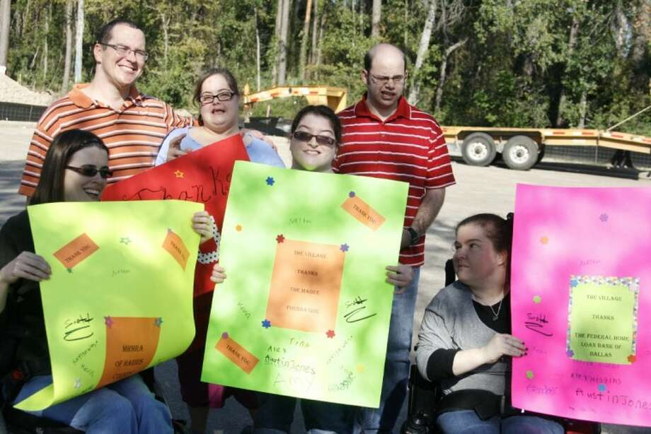 A few of the villagers from the Village Learning and Achievement Center hold up handmade signs thanking supporters at the ground breaking of the Hickory Glen Apartments Oct. 23.