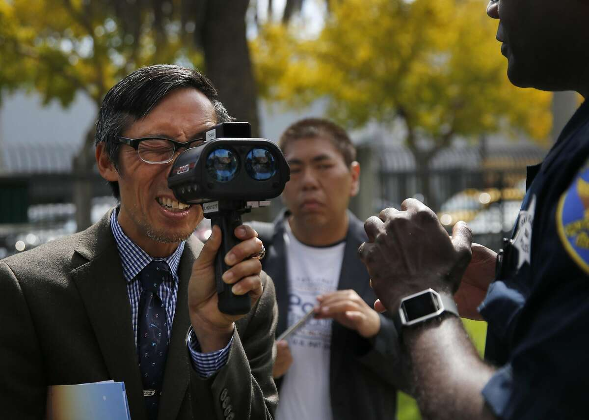 Richmond District Supervisor Eric Mar, left, looks into a LIDAR device of Police Officer Leroy Thomas, right, used to measure speeding cars after a press conference at the Gene Friend Rec Center Sept. 29, 2016 in San Francisco, Calif. SFPD along with SFMTA and Vision Zero announced a renewed effort to catch city speeders by the SFPD.