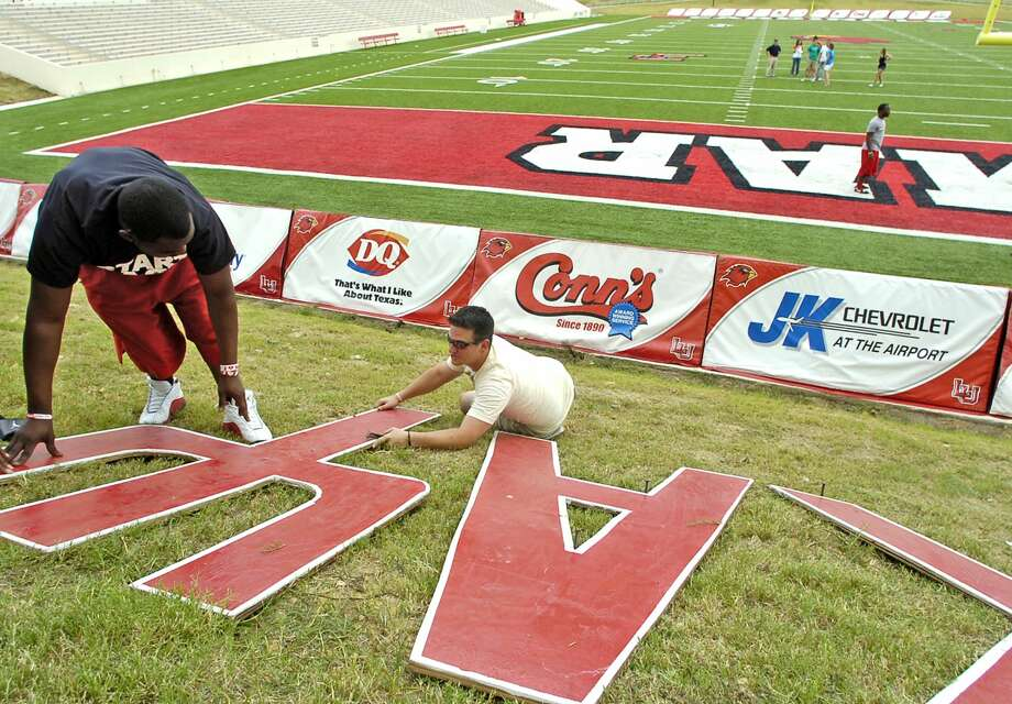The Lamar football stadium real grass had more color added to it Friday afternoon as campus organizations came out and put their fraternities' or sorority' letters on the grassy hill in front of the Montagne Center for the opening game. Nathan Mistric, right, with Sigma Nu, helps Bobby Wilmore Jr. of Kappa Alpha Psi, position the letters for spiking so they would not move.   Dave Ryan/The Enterprise Photo: Dave Ryan/Dave Ryan/The Enterprise