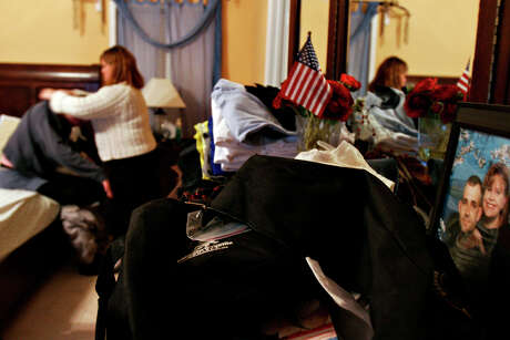 Tammy Edwards undresses her husband Chris, in their north side home, Thursday, November 16, 2006. Staff Sgt. Chris Edwards was injured when a roadside bomb exploded under a dirt bridge while he was on patrol in a Bradley fighting vehicle near Yusufiyah, Iraq.