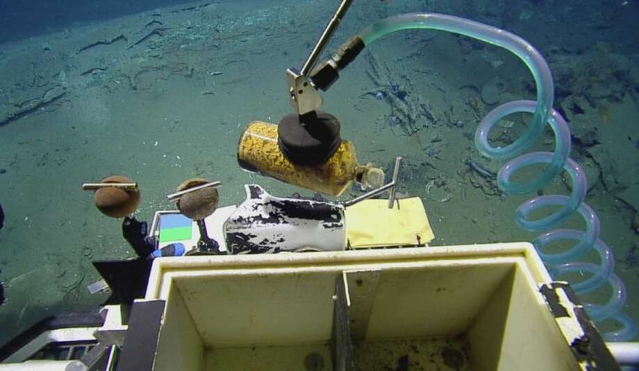A remotely operated vehicle recovers a medicine bottle filled with ginger, a seasickness remedy, from an early 19th century shipwreck recently found in the Gulf of Mexico. The project was funded by a public/private partnership.