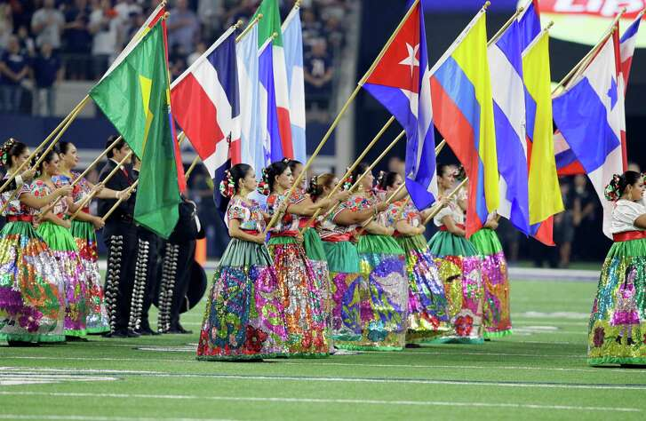 Members of a ballet folklorico and mariachi band from San Antonio, Texas, flags from several latin nations during a ceremony celebrating Hispanic Heritage Month before an NFL football game between the Chicago Bears and Dallas Cowboys on Sunday, Sept. 25, 2016, in Arlington, Texas. (AP Photo/LM Otero)