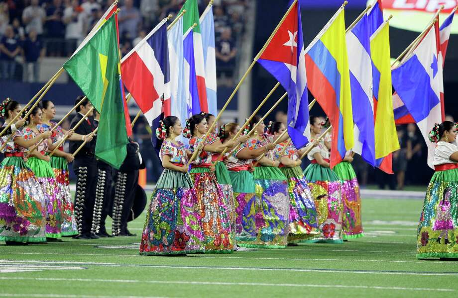Members of a ballet folklorico and mariachi band from San Antonio, Texas, flags from several latin nations during a ceremony celebrating Hispanic Heritage Month before an NFL football game between the Chicago Bears and Dallas Cowboys on Sunday, Sept. 25, 2016, in Arlington, Texas. (AP Photo/LM Otero) Photo: LM Otero, STF / AP