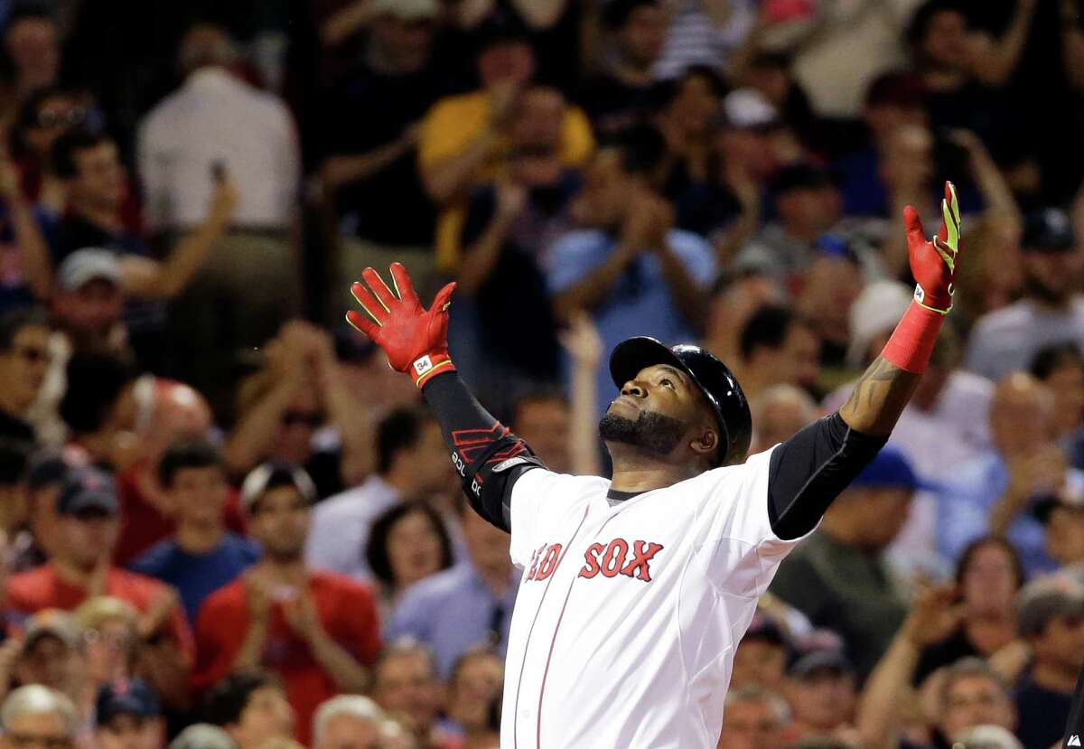 FILE - In this June 24, 2015, file photo, Boston Red Sox designated hitter David Ortiz reacts as he crosses home plate after hitting a two-run home run during the sixth inning of a baseball game against the Baltimore Orioles at Fenway Park in Boston. Ortiz transformed the Boston Red Sox from a cursed franchise to a three-time World Series champion. (AP Photo/Elise Amendola, File)