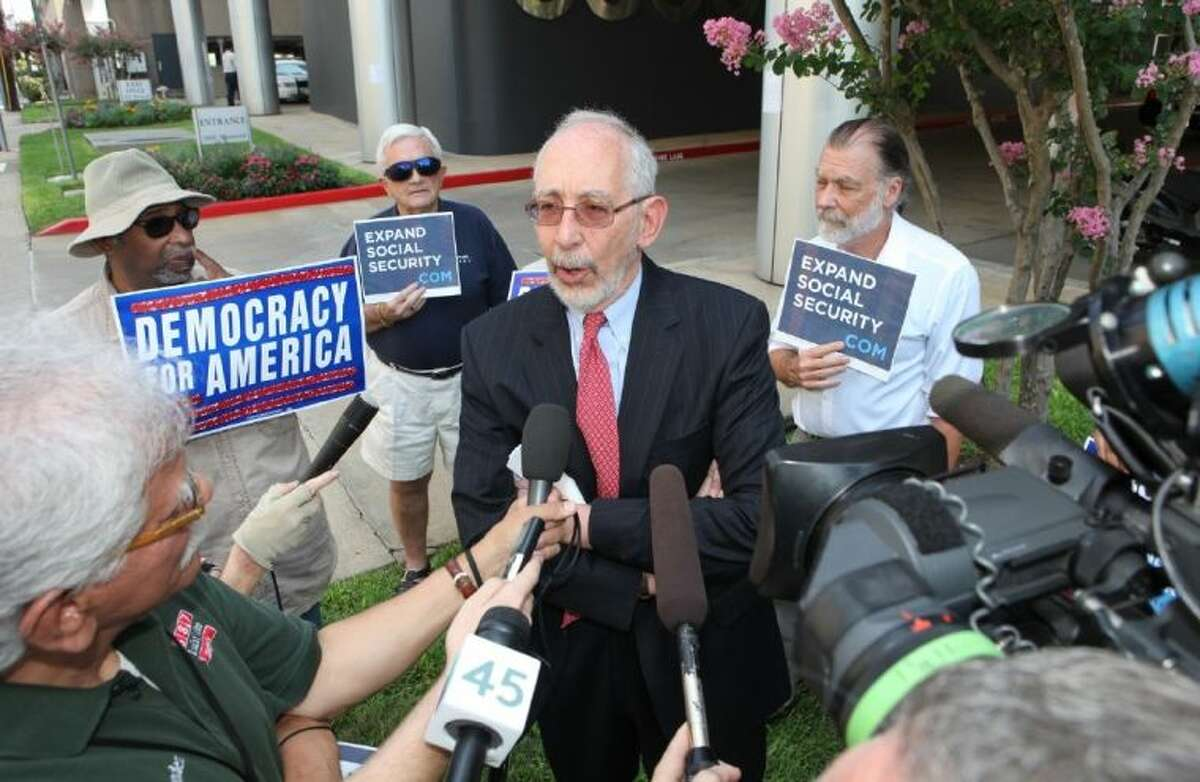 Andy Achenbaum, professor of history and social work at the University of Houston, speaks about Texas voters' support for expanding Social Security benefits, and calling out Senator John Cornyn for supporting benefit-cuts, during a press conference in front of Cornyn's Houston office Thursday, August 1.