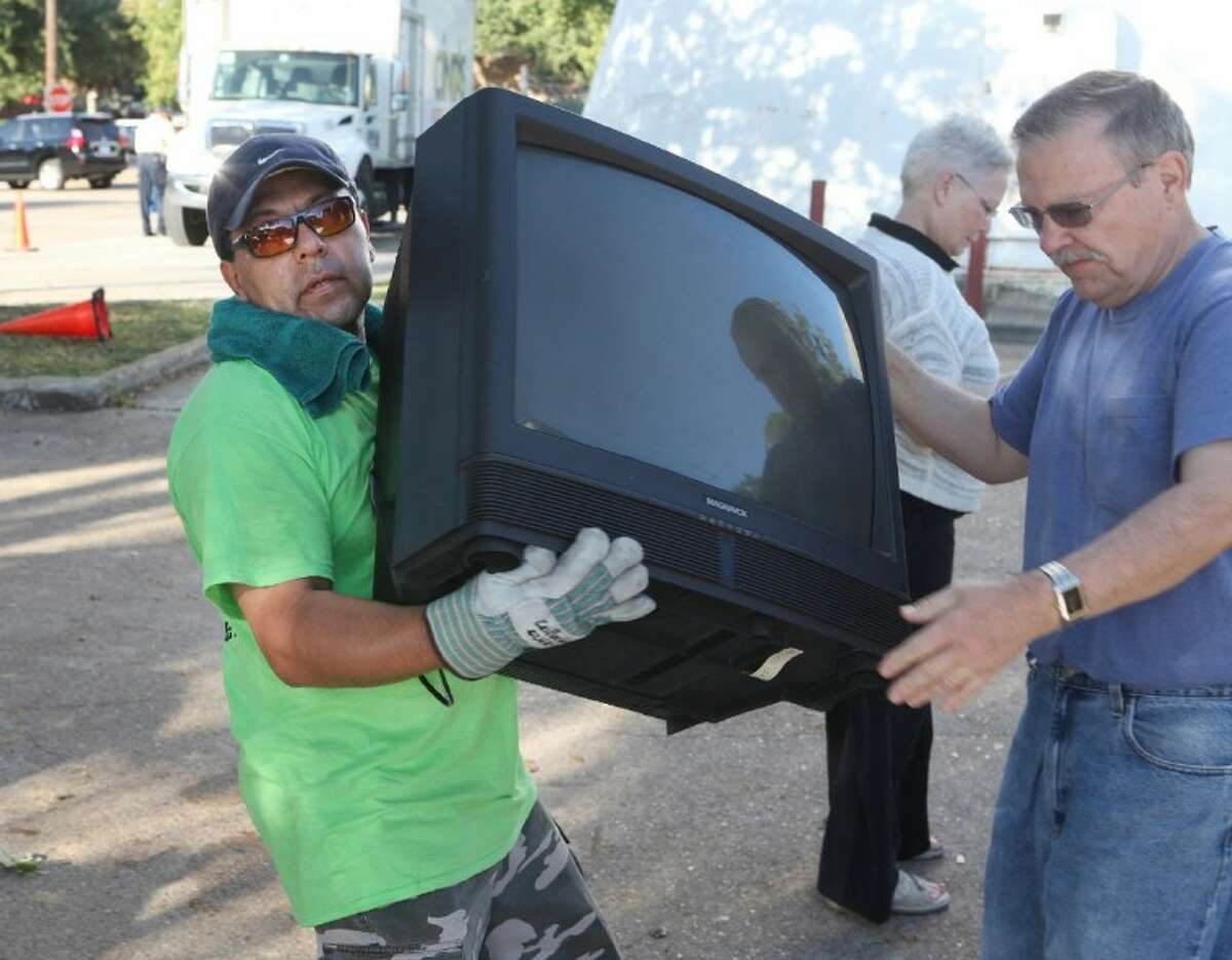Andrew Martinez takes a large television from David Register to be recycled by CompuCycle at Bellaire Recycles Fest in Bellaire on Saturday, Nov. 3.