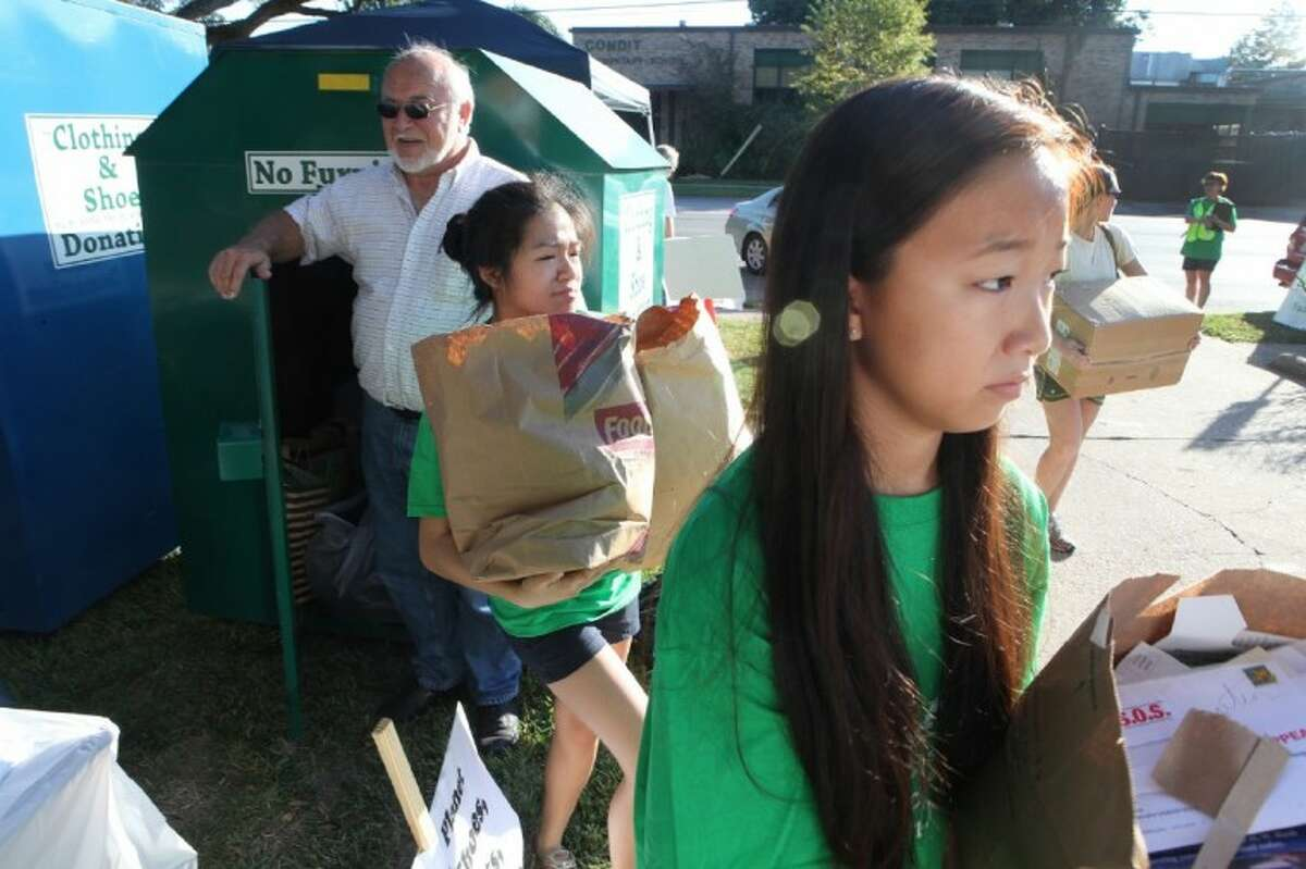 From left, volunteers Amy Nguyen and MJ Jung help deliver bags of paper to be recycled at the Bellaire Recycles Fest.