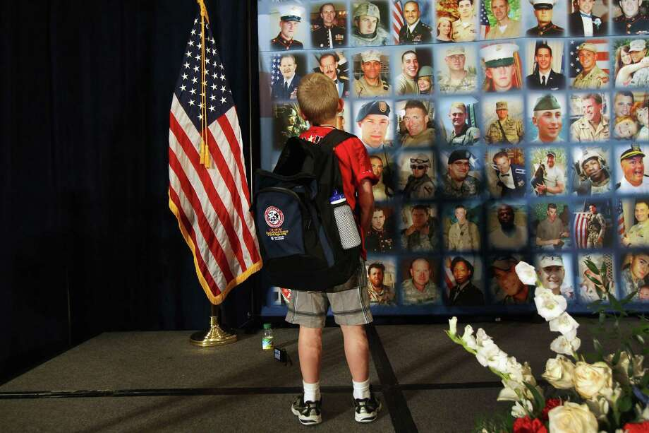 "ARLINGTON, VA- MAY 27: A child looks over portraits of fallen military personel while participating in the TAPS ""Good Grief Camp"" on May 27, 2012 in Washington, DC. (Photo by John Moore/Getty Images) Photo: John Moore /Getty Images / 2012 Getty Images"