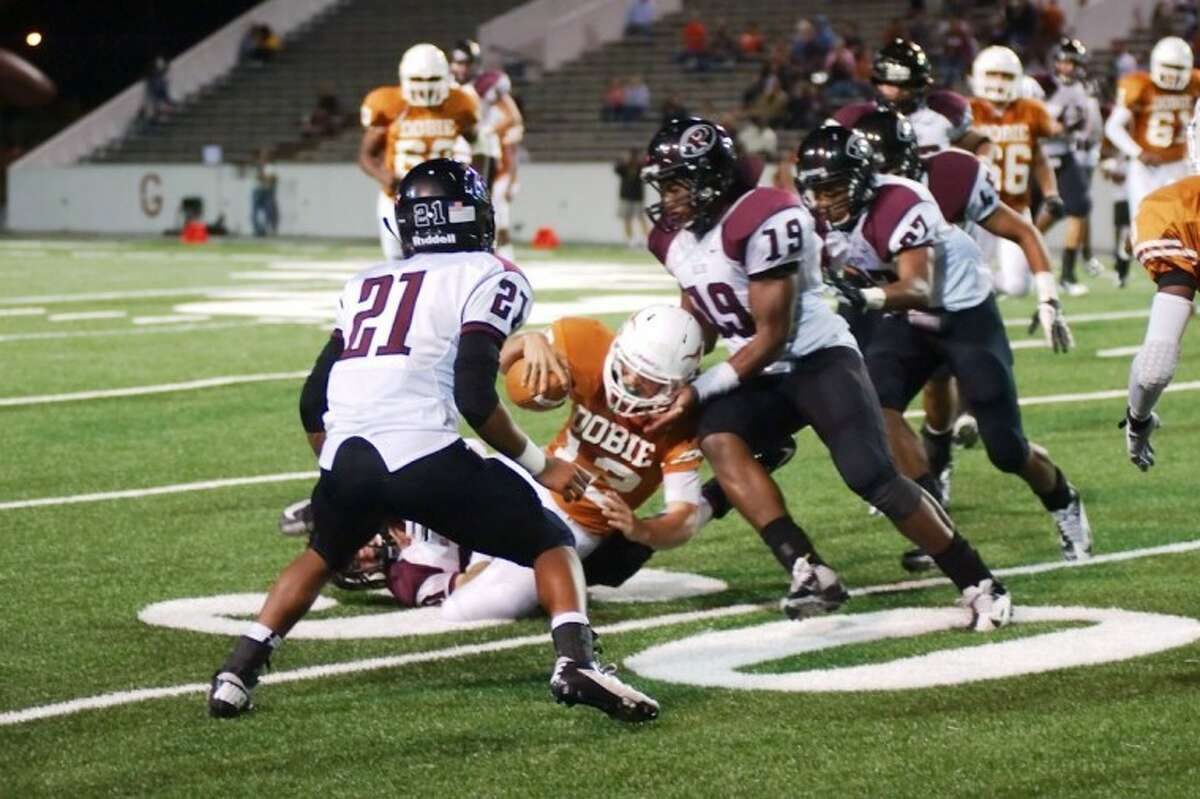Pearland's David Hernandez makes the stop on Dobie quarterback Tyler Wolfe Thursday night in the Oilers' 42-0 win. Pearland defensive back Devante Dodson waits to assist on the play.