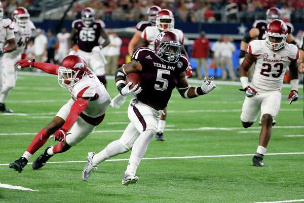 Arkansas defensive back Santos Ramirez, left, is unable to stop Texas A&M running back Trayveon Williams (5) as Williams sprints for the end zone and a touchdown late in the second half of an NCAA college football game, Saturday, Sept. 24, 2016, in Arlington, Texas. Texas A&M won 45-24. (AP Photo/Tony Gutierrez)