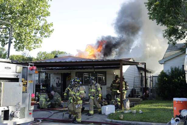 Firefighters battle a house blaze at Scarborough and Comal in Pasadena on Thursday afternoon.