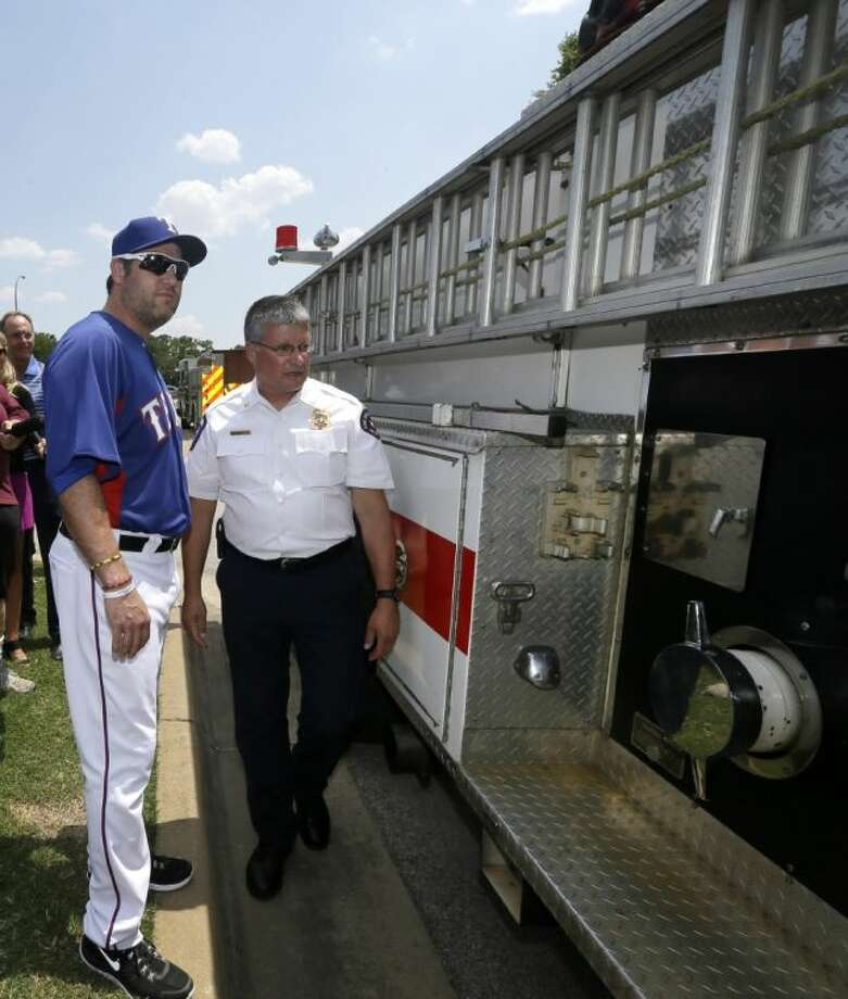 Arlington Fire Department Battalion Chief 3 Bill McQuatters gives Texas Rangers designated hitter Lance Berkman a tour of a Ford commercial pumper fire truck before a game against the Seattle Mariners on July 3 in Arlington. Berkman, with assistance from the City of Arlington Fire Department, donated the fire truck to the West Volunteer Fire Department, which is still recovering from the West Fertilizer Company plant explosion on April 17.