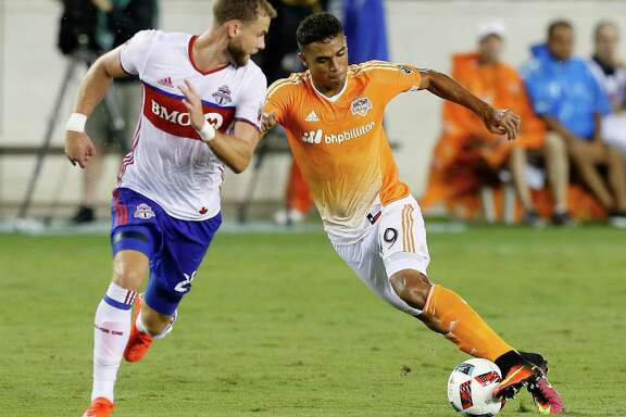Houston Dynamo forward Mauro Manotas (19) dribbles behind Toronto FC defender Josh Williams (23) as he brings the ball up the field during the second half during an MLS soccer match Sunday, Aug. 14, 2016, in Houston. Toronto FC and Houston played to a 1-1 draw. (AP Photo/Bob Levey)