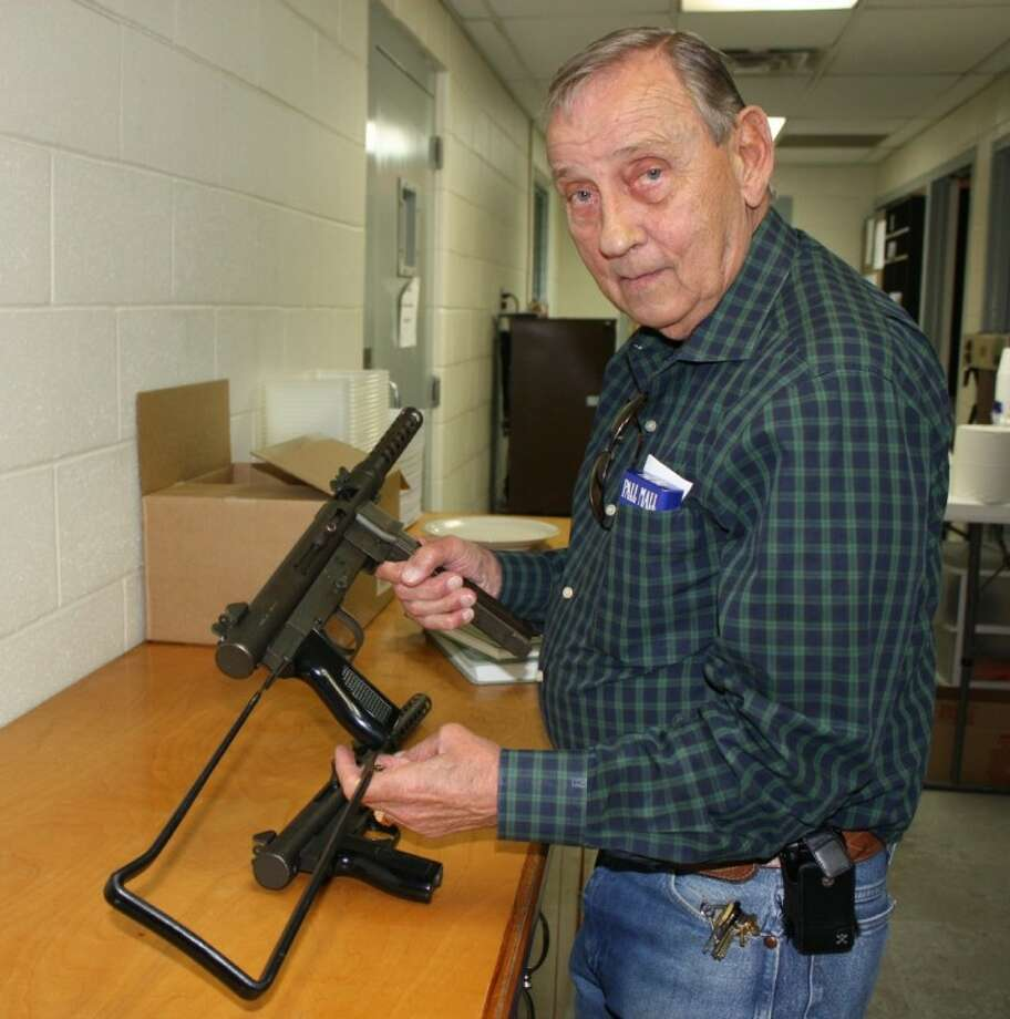 Chief Robert Long, of the San Jacinto County Sheriff's Office, extends the folding stock on a Smith & Wesson 9 mm submachine gun that is being sold by the department to buy equipment.