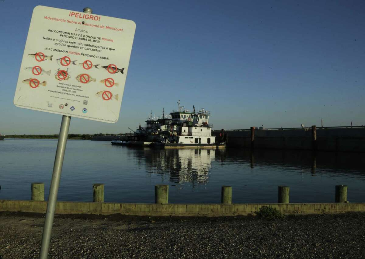 Signs near the San Jacinto River waste pits warn people not to enter or consume fish from the area.