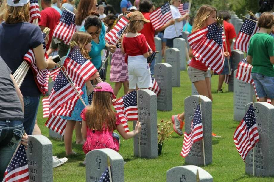 Students from Magnolia ISD place flags on the graves of soldiers at Houston National Cemetery last Memorial Day. The students visited the cemetery as part of Flags for Our Heroes. The group is currently collecting change to purchase flags for next Memorial Day. They will collect through Feb. 8. Photo: Submitted Photo