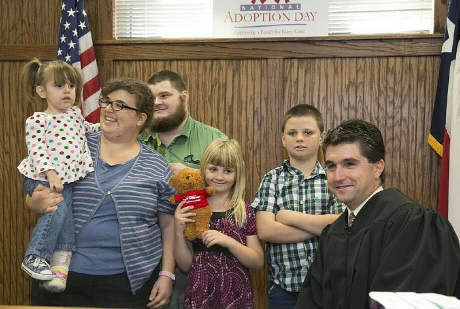 Hayleigh, 2, left, is the newest member of the Charles and Tabitha Hickman family of Conroe following an adoption hearing administered by 418th state District Judge Tracy Gilbert, right, on National Adoption Day Nov. 14.