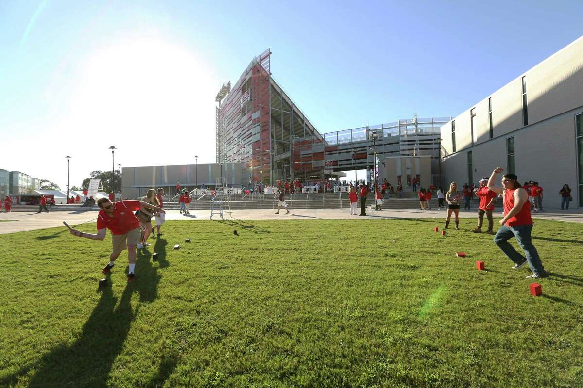 University of Houston fans play games outside of the TDECU Stadium before the team takes on University of Connecticut Thursday, Sept. 29, 2016, in Houston.