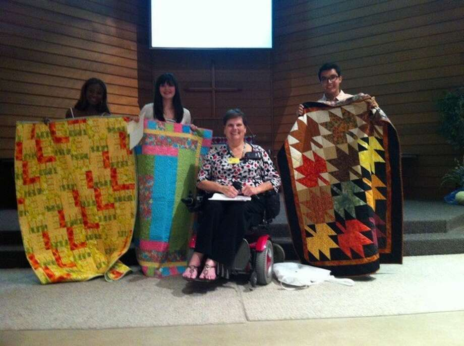 The Kingwood Area Quilt Guild honored three local students by providing them with scholarships for college. From left, Adetoun Taiwo, a graduate of Humble High School; Caroline Rosson, a graduate of Kingwood Park High School; Kingwood Area Quilt Guild education chairperson Brenda Howard; and Daniel Carvajal, a graduate of Kingwood Park High School.