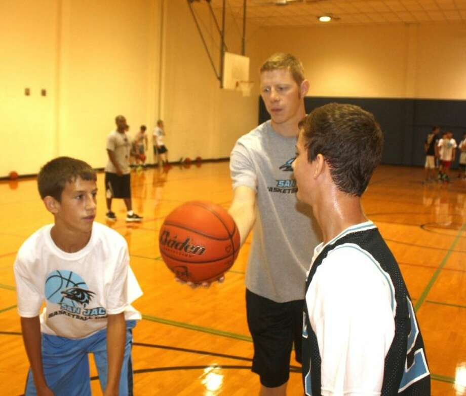 Former Deer Park High School standout player Ryan Bright prepares the jump ball for Kolton Fowler (left) and Jake Matejka during the opening day of the San Jacinto College youth basketball camp Monday.