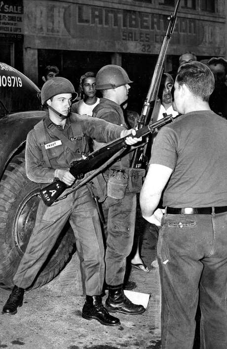 Jay Frank, a Progressive Labor party demonstrator, is held at bay by a National Guardsman at 14th and Mission streets on Sept. 28, 1966. Photo: Duke Downey, The Chronicle