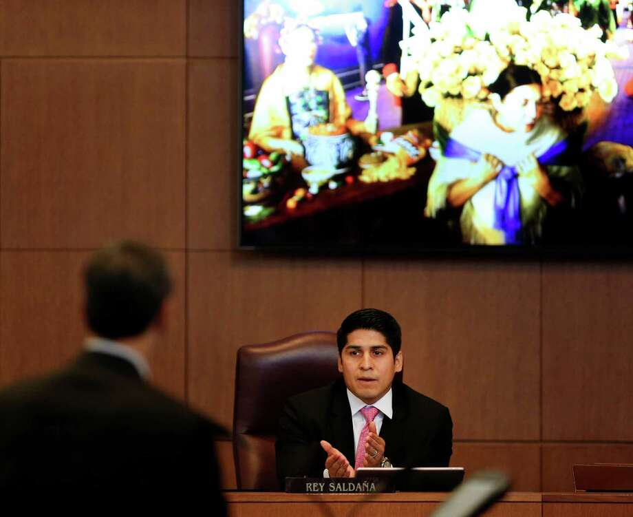 A proposed but unused ad from a 2012 ad campaign, seen on a screen behind council member Rey Saldana, depicts a hispanic woman carrying a basket of flowers. Saldana displayed the image as he expressed his concerns for funding the newly created Visit San Antonio. The city council voted to fund the former convention and visitors bureau with about $24 million. The CVB has shifted from a city department to a private organization funded by the city, called Visit San Antonio. Photo: William Luther /San Antonio Express-News / © 2016 San Antonio Express-News