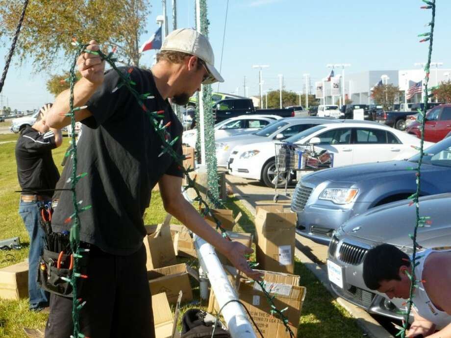 Workers help set up Christmas lights at Northwest Dodge.