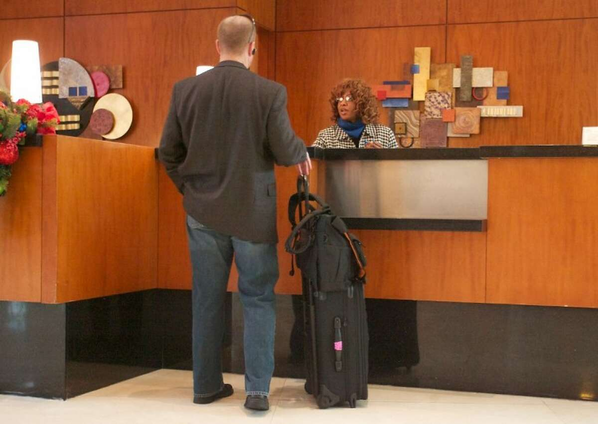 Front desk manager Charlotte Clark helps a guest check-in at The Woodlands Waterway Marriott Hotel and Convention Center Tuesday.