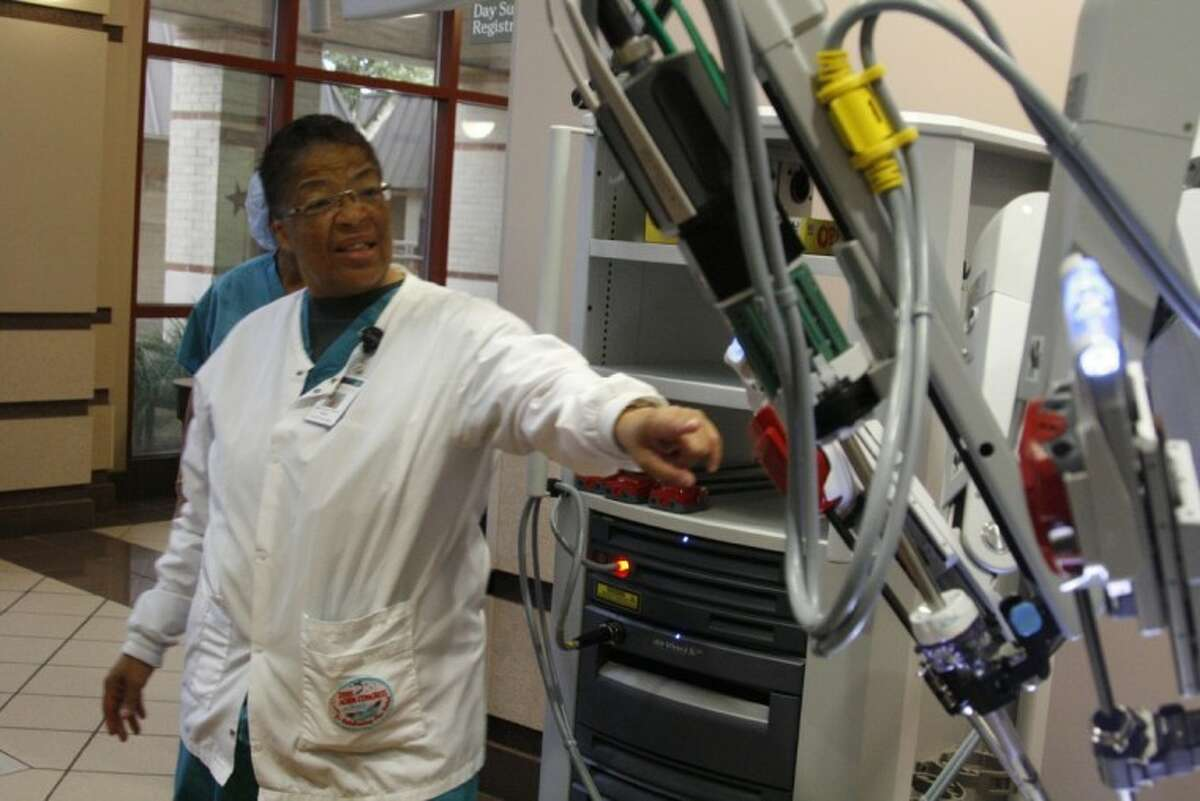 Rose Sams with Memorial Hermann Northeast's sterile processing department, explains how the da Vinci robot system works to fellow employees at the ribbon cutting ceremony for the system Nov. 29.