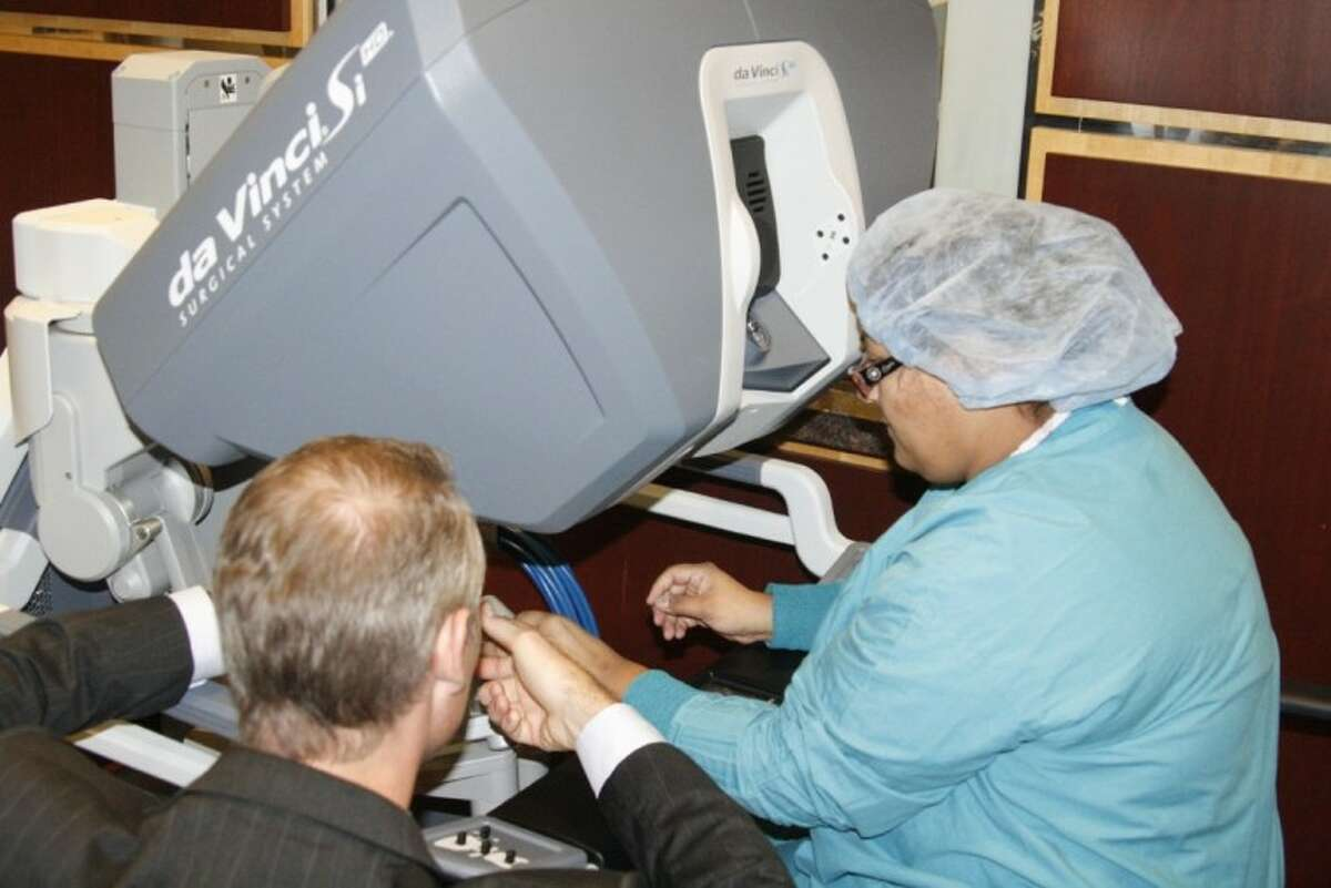 A Memorial Hermann Northeast employee practices how to use the da Vinci robot system with the help of Brian Kiscoe of Intuitive Surgical Nov. 29.