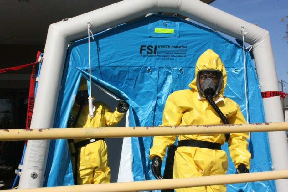 Employees of the Cleveland Regional Medical Center don chemical protection suits for a training exercise on Nov. 29 to simulate a chemical contamination scenario. Photo: MELECIO FRANCO