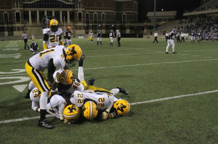 Thoughts: Right after Marshall defensive back Dominique Roberson recovered an Elgin fumble on the last play of the game, he was mobbed by teammates. The contrast between the Marshall players celebrating in the foreground and the Elgin players body language in the background makes for a compelling image.See view more photos from the game:http://bit.ly/QD6J0kCaption: Marshall defensive back Dominique Roberson (14) is mobbed by teammates after recovering a Elgin fumble on the final play of the game during a UIL Division II, Region III-4A regional high school playoff game at the Berry Center on Dec. 1, 2012, in Cypress, Texas. Marshall defeated Elgin 31-28. (AP Photo/The Courier, Jason Fochtman) Photo: Jason Fochtman