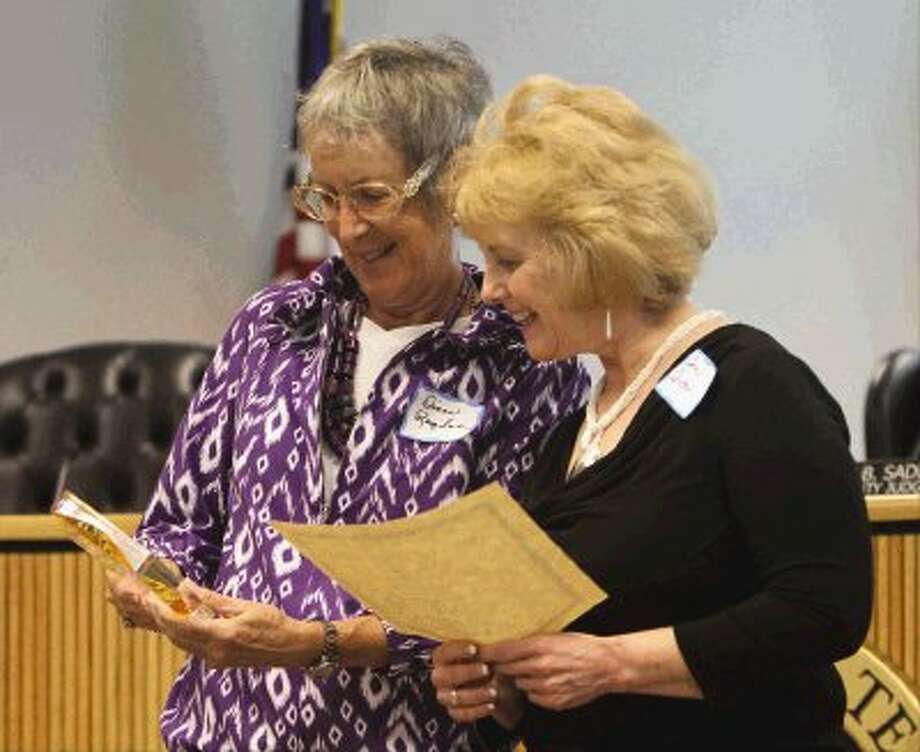 Diane Ragsdale, left, looks over the award she received from Judge Claudia Laird for her service during the inaugural Guardian Angel Day reception honoring guardians, court visitors and attorneys ad litem who assist in cases concerning residents with special needs Wednesday. / Conroe Courier
