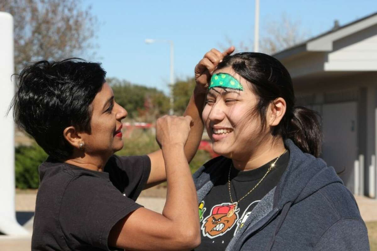 Padmaja Vedartham, left, a biology professor at Lone Star College System-CyFair, paints Shoshana Naftel's face at a dodgeball tournament held for her benefit on Nov. 24.