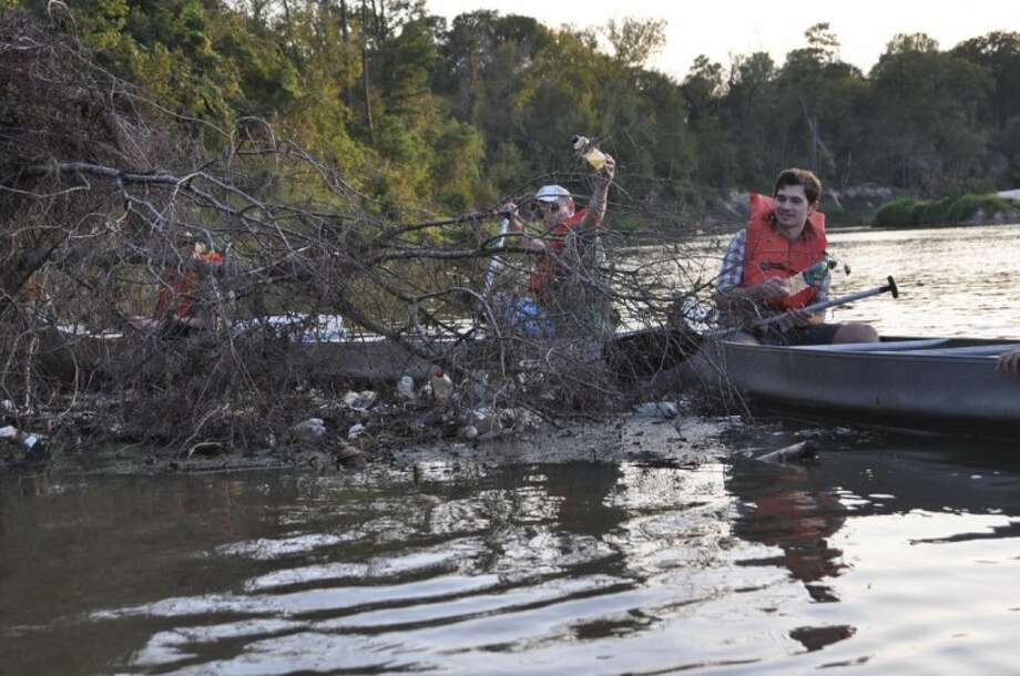 Bayou Land Conservancy members remove bottles from Spring Creek during a Bayou Land Conservancy Event.