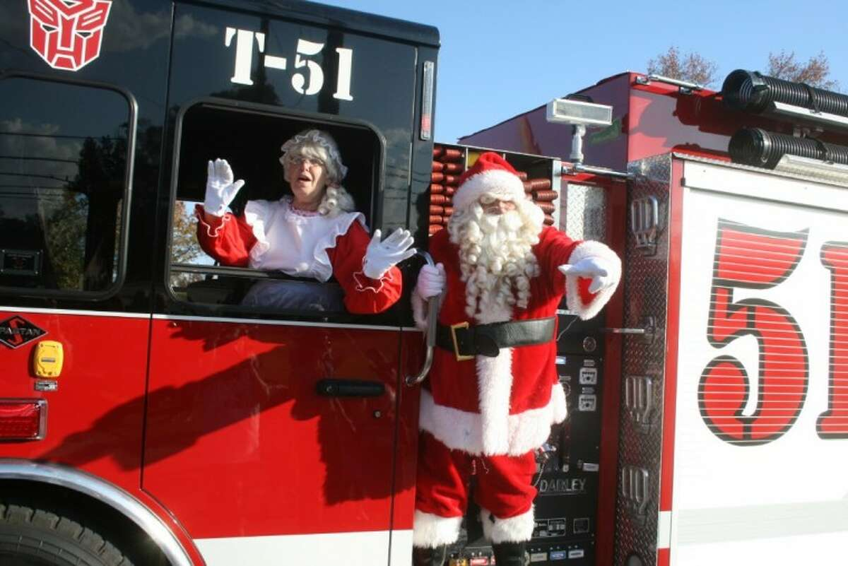Santa and Mrs. Claus wave hello to all the boys and girls, young and old, as he made his grand entrance on one of the Huffman Volunteer Fire Department trucks.