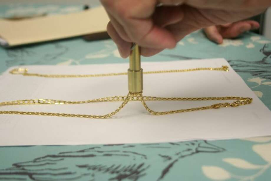 """John E. Morton's 14kt gold necklace reacts to a """"gold magnet"""" test. Photo: Nate Brown"""