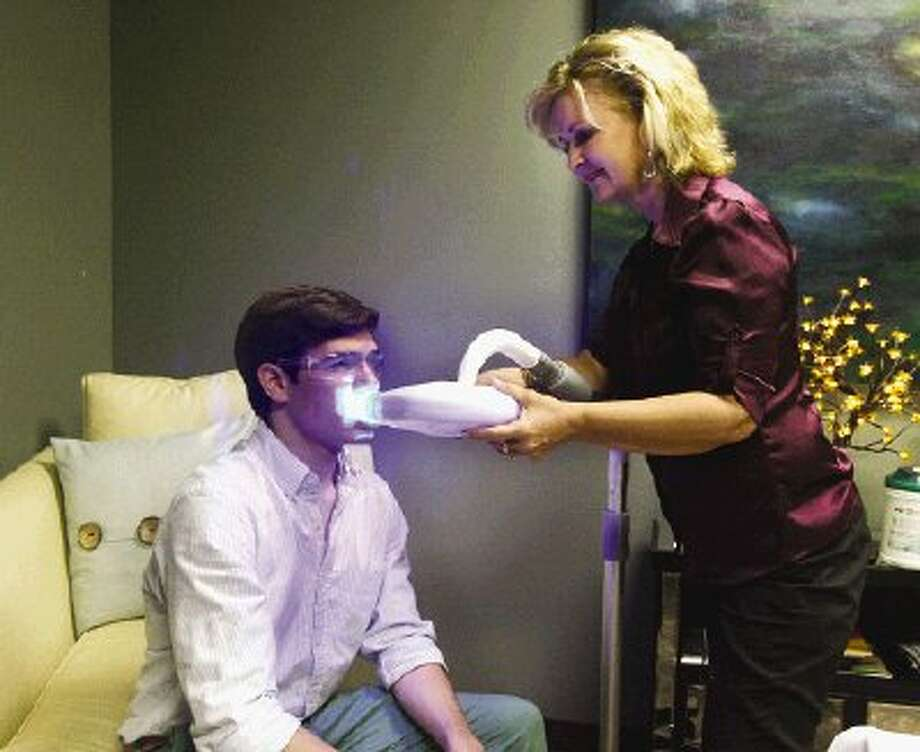 Body Benefits owner Sherry Summers, right, positions the NUYU teeth whitening system for Daniel Espindola, a 20-year-old student at Lone Star College-Montgomery.