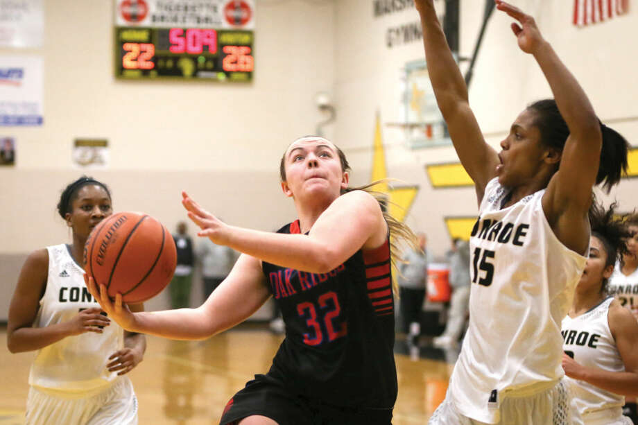 Oak Ridge's Kelsey Scibek (32) goes for a layup while Conroe's Natayla Nance (15) during the high school girls basketball game on Tuesday, Jan. 6, 2015, at Conroe High School. To view or purchase this photo and others like it, go to HCNPics.com.