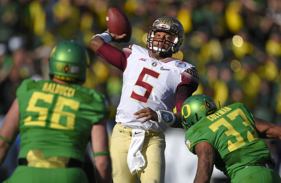 Florida State quarterback Jameis Winston, center, looks to pass under pressure by Oregon defensive lineman Alex Balducci, left, and Tyson Coleman during the first half of the Rose Bowl NCAA college football playoff semifinal, Thursday, Jan. 1, 2015, in Pasadena, Calif. (AP Photo/Mark J. Terrill) Photo: Mark J. Terrill