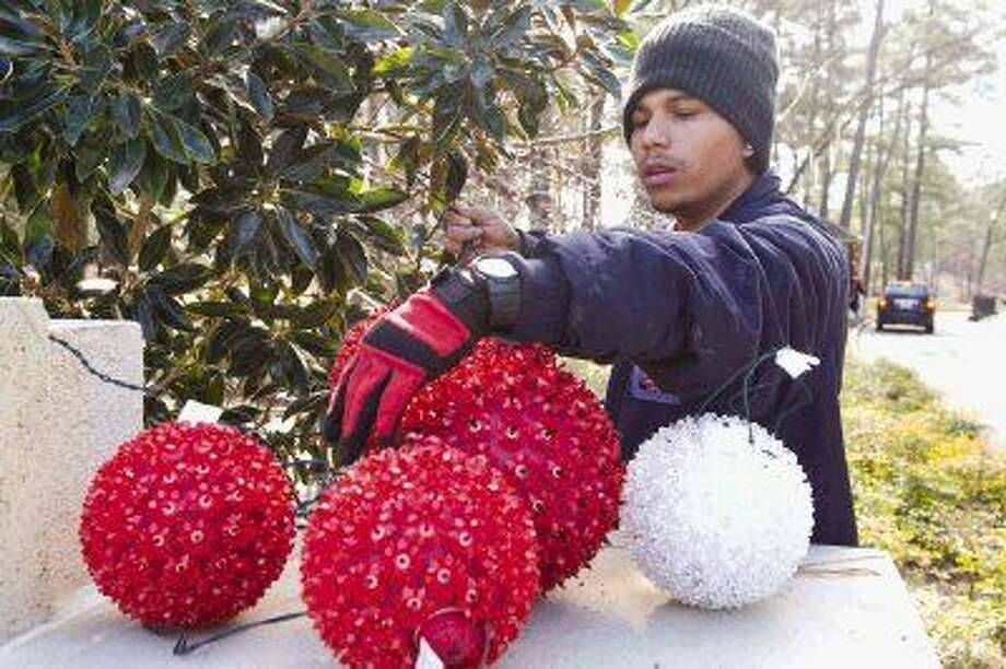 Joel Flores bundles up to help take down Christmas decorations in front of Bentwater Country Club Tuesday. Temperatures are expected to dip into the 30s with the possibility of freezing rain through Saturday. Photo: Jason Fochtman