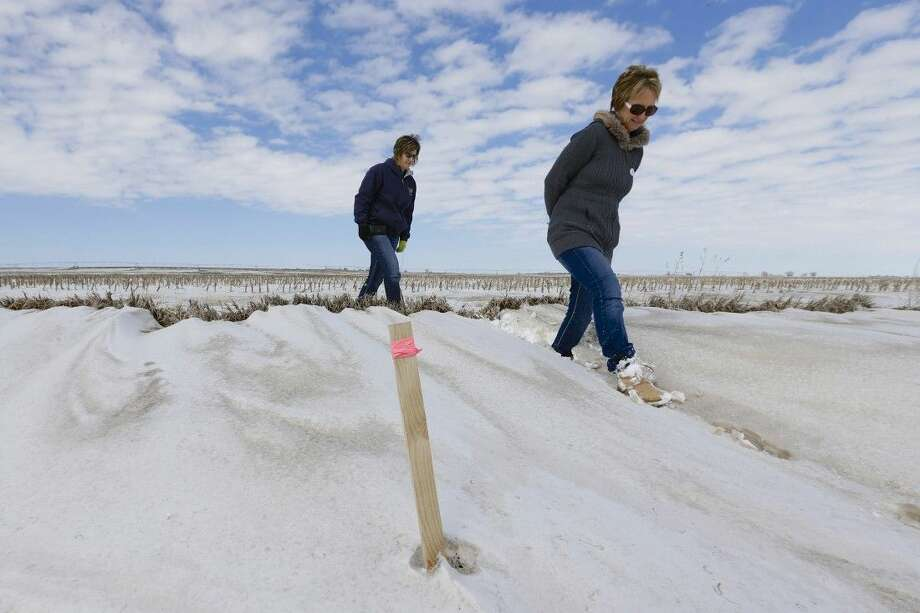 Sisters Jenni Harrington, left, and Abbi Kleinschmidt on March 11, 2013, pass a stake that marks the proposed route of the Keystone XL pipeline on Harrington's property near Bradshaw, Neb. Photo: Nati Harnik