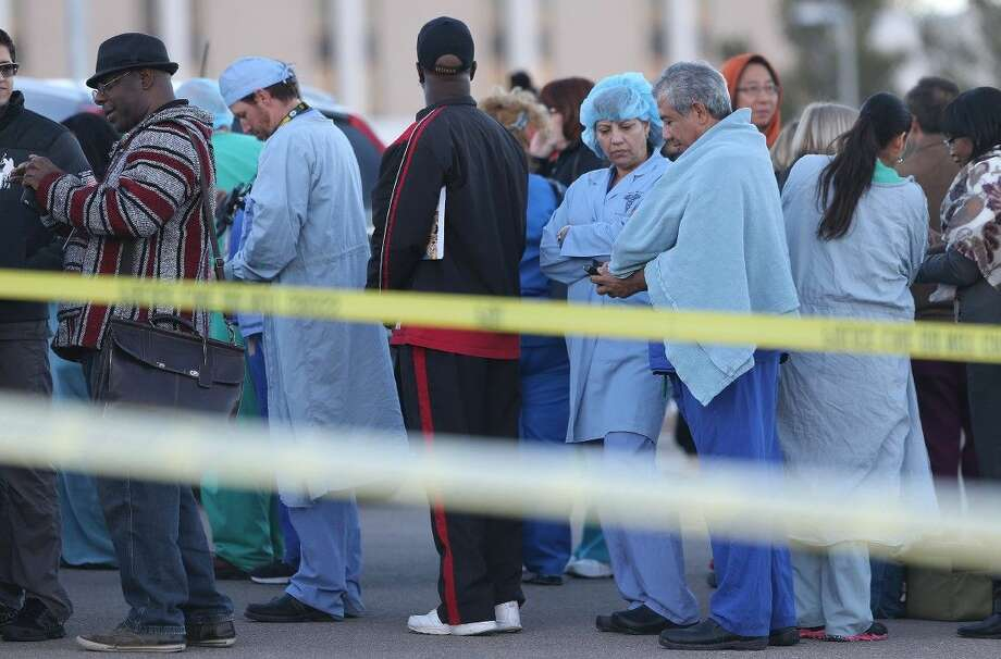 Medical personnel wait with VA and Beaumont Army Medical Center visitors in a parking lot following a shooting inside the El Paso facility Tuesday.