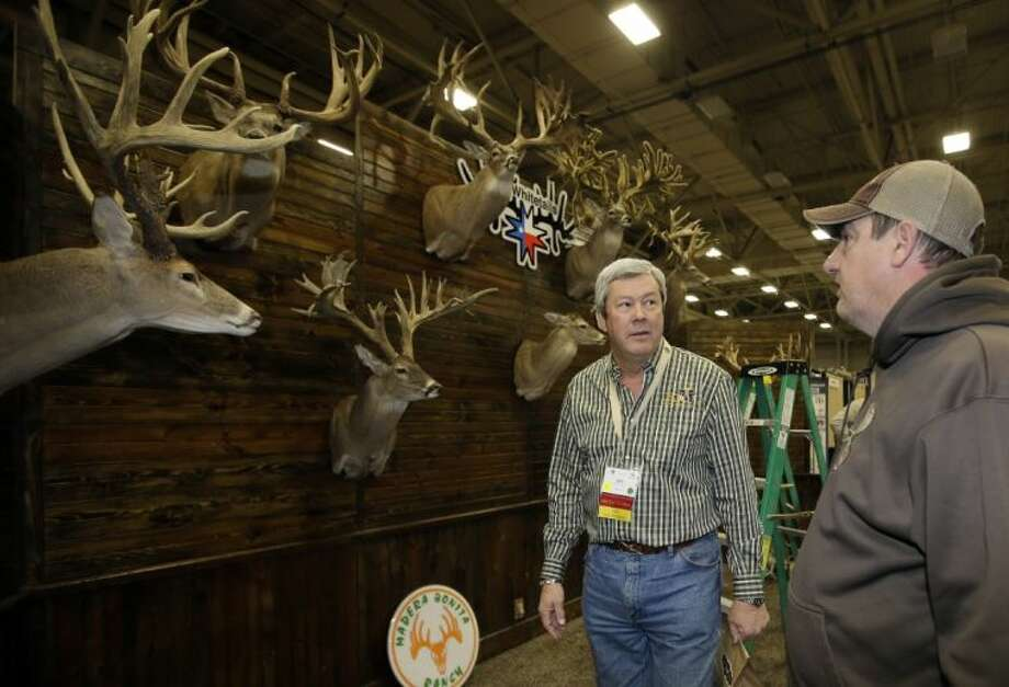 Dallas Safari Club executive director Ben Carter talks with Mike Woods of 4JM White Tails Hunting in the Dallas Exhibit Hall as set up continues for the clubs weekend show Wednesday in Dallas. The FBI is investigating death threats made against members of the Dallas Safari Club, which intends to auction off a rare permit to hunt an endangered black rhino, an FBI spokeswoman said Wednesday.
