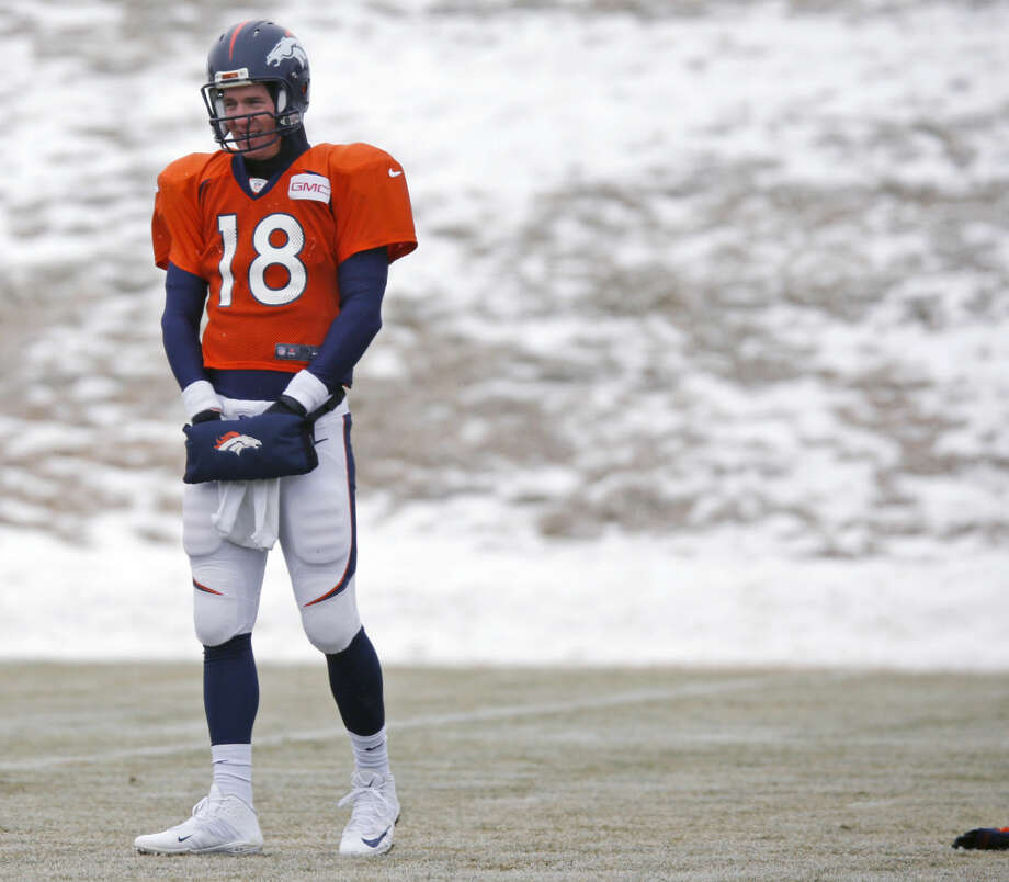Denver Broncos quarterback Peyton Manning keeps his hands warm in a pouch while waiting to throw the football during practice for the team's NFL divisional playoff game against the Indianapolis Colts on Wednesday. Photo: AP Photo By David Zalubowski