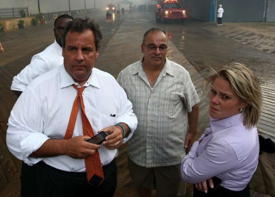 """In this Sept. 12, 2013 photo provided by the Office of the Governor of New Jersey, Deputy Chief of Staff Bridget Anne Kelly, right, stands with Gov. Chris Christie, left, during a tour of the Seaside Heights, N.J. boardwalk after it was hit by a massive fire. Christie fired Kelly Thursday and apologized over and over for his staff's """"stupid"""" behavior, insisting during a nearly two-hour news conference that he had no idea anyone around him had engineered traffic jams as part of a political vendetta against a Democratic mayor."""