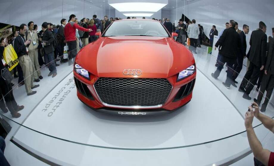 Trade show attendees gather around the Audi Sport quattro laserlight concept car at the International Consumer Electronics Show Wednesday in Las Vegas. The car is outfitted with laser lights offering three times the illumination as LED lights.